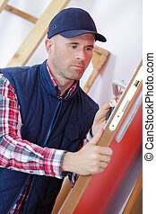 male carpenter worker at interior wood door lock installation