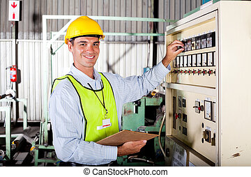 technician setting up industrial machine - male caucasian...
