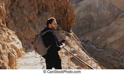 Male Caucasian tourist on ancient mountain road. Man with...
