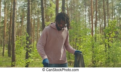Handsome environmentally friendly african american male charity volunteer in protective gloves with garden tool and trash bag picking up litter in forest, caring for nature and preserving ecology.