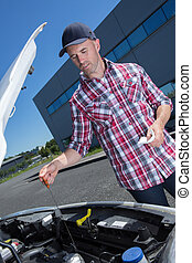 male checking the oil level of his car