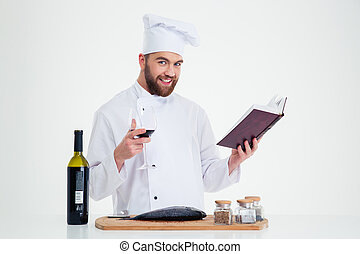 Male chef cook holding recipe book and glass with red wine