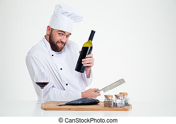 Male chef cook preparing fish and holding bottle with red wine
