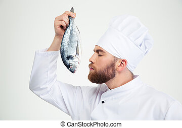 Male chef cook smelling fresh fish - Portrait of a male chef...