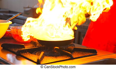 Male chef cooking flambe style dish on pan in modern kitchen...