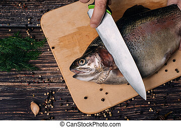 male chef cuts raw trout on a wooden Board