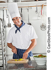 Male Chef Cutting chili In Kitchen