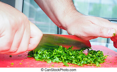 Male chef cutting parsley with big knife on red chopping board