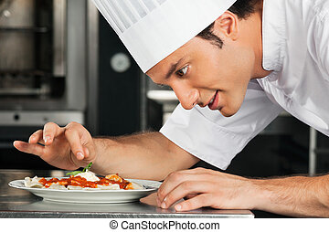 Male Chef Garnishing Dish - Side view of male chef...