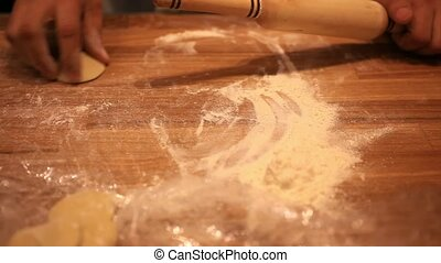 male chef hands preparing dough with rolling pin for asian food on wooden board at kitchen counter in bakery. HD. 1920x1080