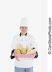 Male chef holding fresh breads in basket