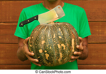 Male chef holding pumpkin and knife