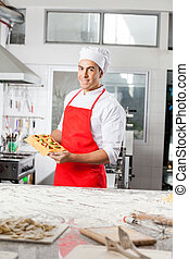 Male Chef Holding Tray With Stuffed Ravioli Pasta Sheet