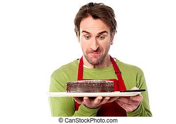 Male chef holding yummy chocolate cake