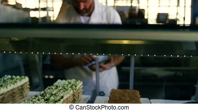Male chef maintaining records in bakery shop 4k
