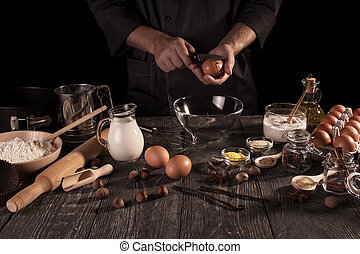 Male chef prepares fragrant cake with lots of spices. Dark key