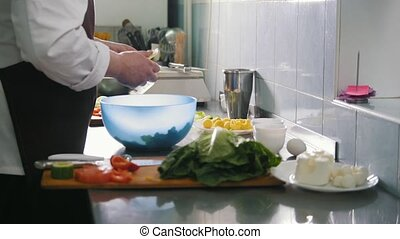 Male chef preparing salad in commercial kitchen, close-up