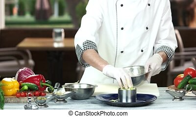 Male chef preparing salad.