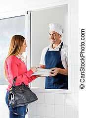 Male Chef Selling Pasta Packets To Woman