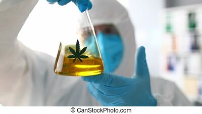 Male chemist mixing yellow liquid sbd oil closeup. Medical ...