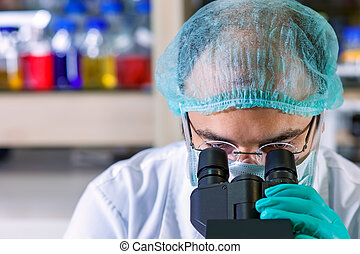 Male chemist working in a laboratory wearing glasses, a surgical cap and mask looking down the ocular of his microscope as he performs an analysis close up of his head.