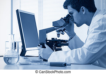 laboratory - male chemist working with microscope in...