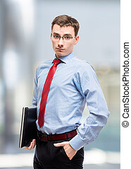 Male chief accountant with laptop posing in office