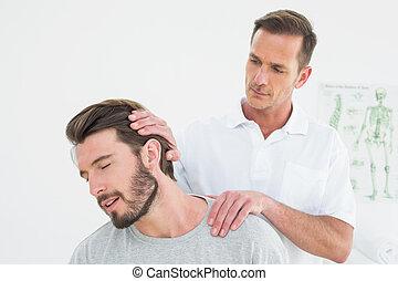Male chiropractor doing neck adjust