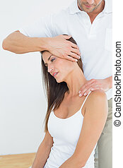 Male chiropractor doing neck adjustment in the medical...