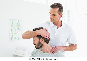 Male chiropractor doing neck adjustment