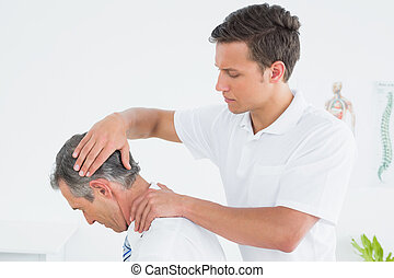 Male chiropractor doing neck adjustment - Side view of a...