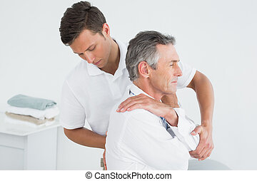 Male chiropractor examining mature man