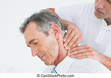 Male chiropractor massaging patients neck