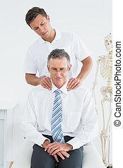 Male chiropractor massaging patients neck