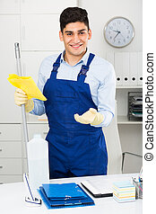 Male cleaner 25-30 years old is ready to clean the cabinet in office.