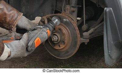 Male Cleans rust brake electric drill caliper before...