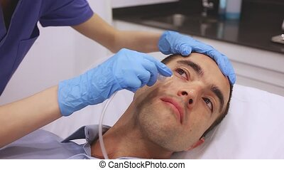 Young man receiving innovative anti-aging carboxytherapy procedure for facial skin in aesthetic medicine cabinet, infusing of carbon dioxide