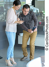 male client with female seller in furniture store