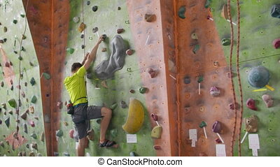 Male climber climbs the cliff wall in the room reaching and...