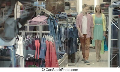 Male Clothes Department - A young couple choosing a male...