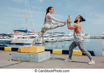 Male coach helping young woman exercising on pier.