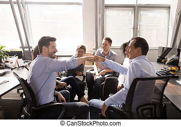 Male colleagues fist bumping at company meeting, business briefing