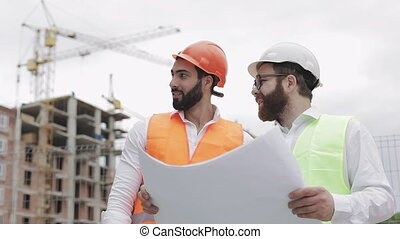 Male construction engineer discussion with architect at construction site or building site of highrise building. They holding construction drawings in their hands.
