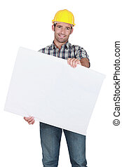 Male construction worker holding blank advertising board
