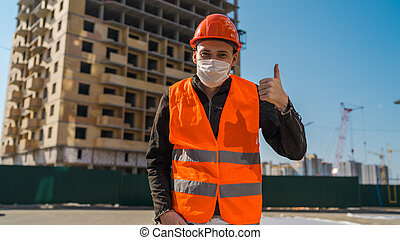 Male construction worker in overalls and in medical mask showing thumbs up on background of house under construction. Young man in hard hat and orange vest showing gesture of approval.