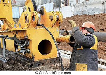 Male construction worker on a construction site work repairing special equipment for trenching and excavation