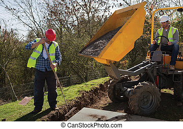 Male construction workers using heavy machinery