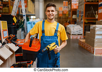 Male constructor holds tools in hardware store