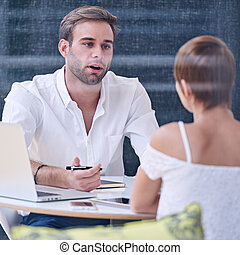 Male consultant mid speech during presentation with his female client