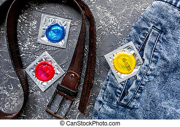 male contraception with condom in jeans on dark background top view